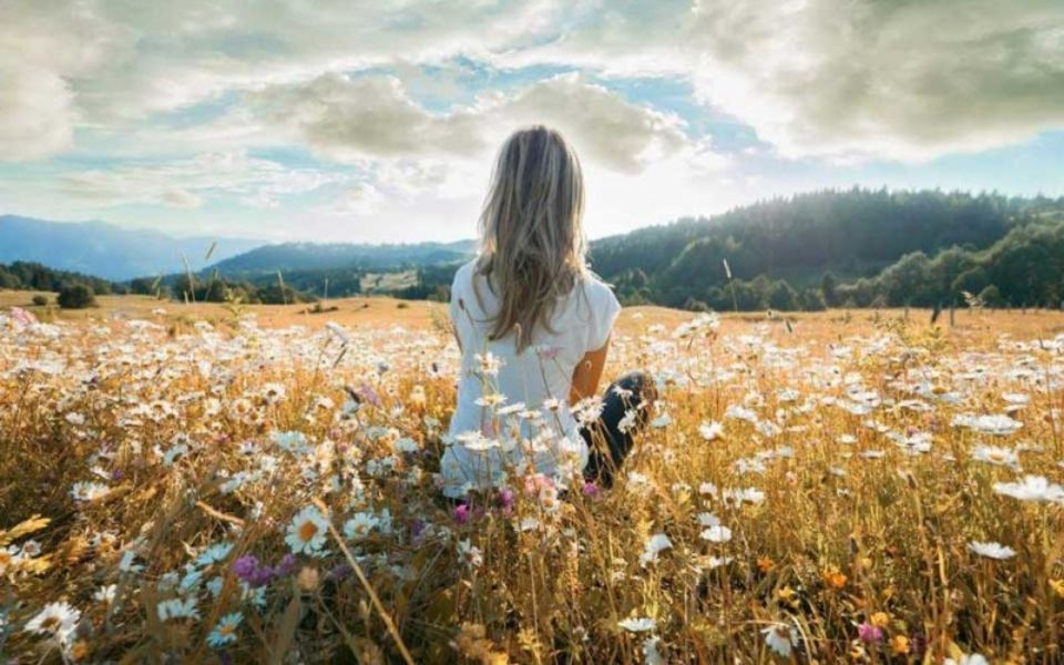 Woman meditating in a field of daisies