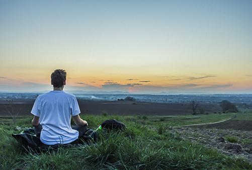 Man meditating in grass